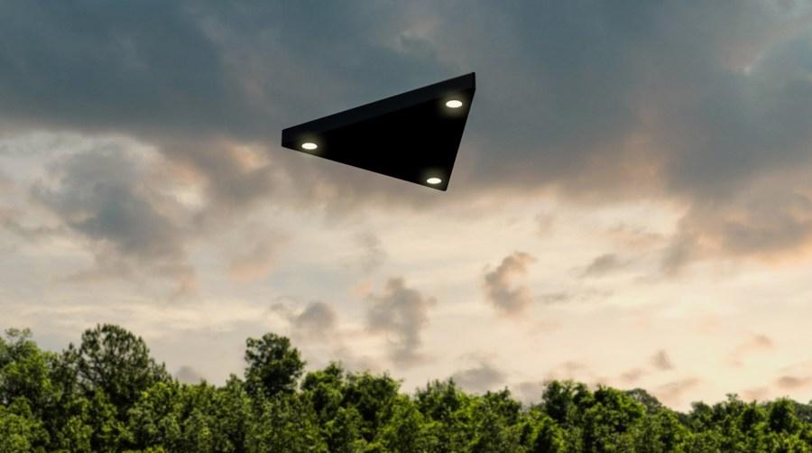 Black, triangular UFO flies above the trees