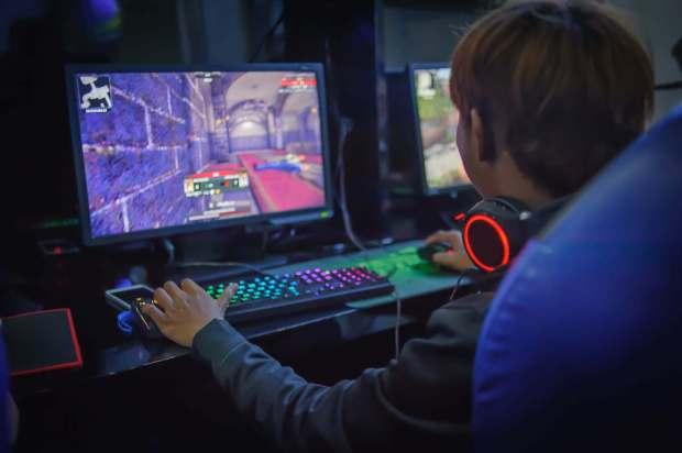 Un niño jugando a un videojuego en un café de computadora.