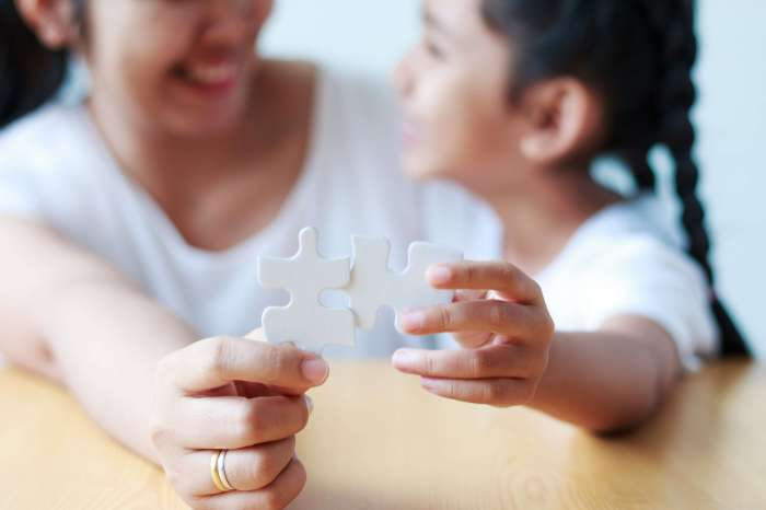 Un padre y un niño sosteniendo dos piezas de un rompecabezas que no encajan