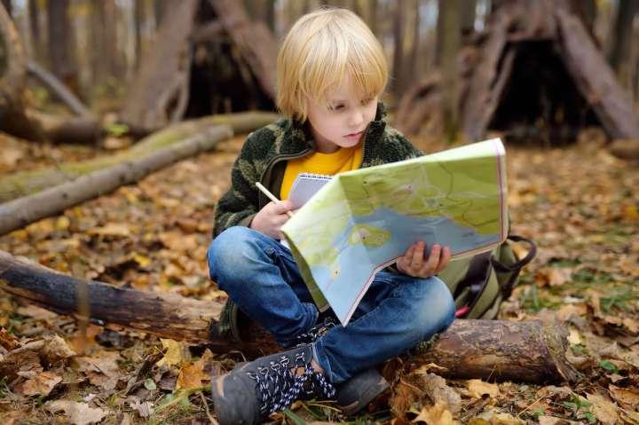 Un niño leyendo un mapa, una de las actividades desconectadas que se benefician de estos conceptos básicos de codificación.