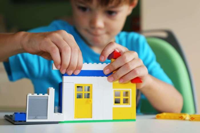 Un niño construye un muro de lego.