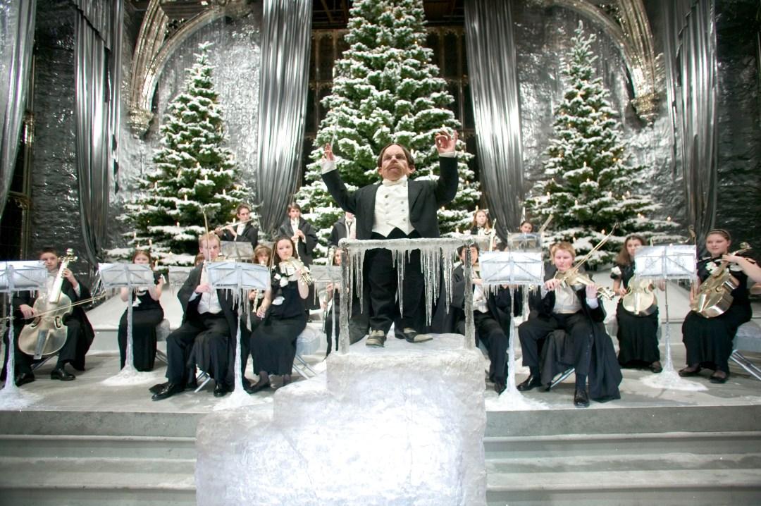 V pozadí tři velké vánoční zasněžené stromky. Před nimi orchestr a v popředí dirigující profesor Kratiknot.