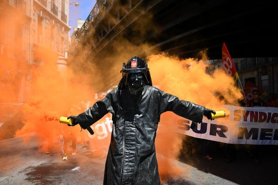 TOPSHOT - A man wearing a Dark Vador mask holds smoke flares during a demonstration against the French government's planned labour law reforms, on June 2, 2016 in Marseille, southern France. .France suffered a third day of rail strikes on June 2, 2016, but fears of transport chaos during the Euro 2016 football tournament eased as airport workers cancelled a walkout and a Paris subway strike had little impact. More demonstrations against the reforms -- which the government says are designed to make France more business-friendly -- took place in major cities on June 2 and workers were back on strike at 16 of the country's 19 nuclear power stations.. / AFP / ANNE-CHRISTINE POUJOULAT        (Photo credit should read ANNE-CHRISTINE POUJOULAT/AFP/Getty Images)