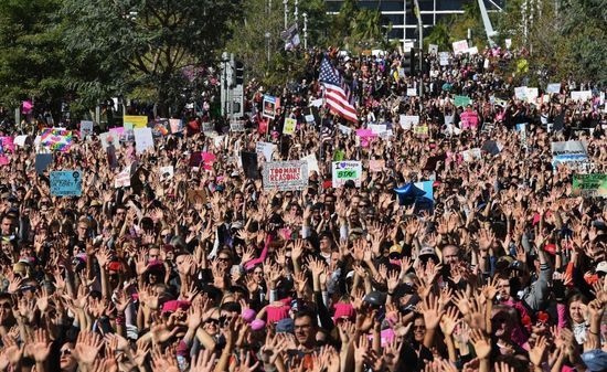 """Protesters, part of a 500,000 strong crowd, attend the Women's Rally on the one-year anniversary of the first Women's March in Los Angeles, California on January 20, 2018..Protestors took to the streets en masse across the United States Saturday, hoisting anti-Donald Trump placards, banging drums and donning pink hats for a second Women's March opposing the president -- one year to the day of his inauguration. Hundreds of thousands of marchers  assembled in Washington, New York, Chicago, Denver, Boston, Los Angeles and other cities nationwide, many donning the famous pink knit """"pussy hats"""" -- a reference to Trump's videotaped boasts of his license to grope women without repercussions.. / AFP PHOTO / Mark RALSTON        (Photo credit should read MARK RALSTON/AFP/Getty Images)"""