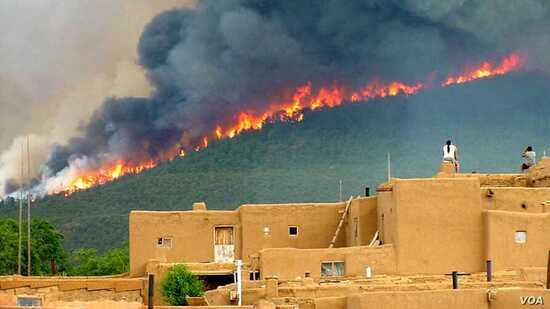 Pueblo tribal members watch the Encebado Fire on Taos Pueblo land in New Mexico, July, 2003. The fire, sparked by lightening, burned 5,000 acres near the Pueblo, leading to subsequent flooding and erosion when rain finally fell.
