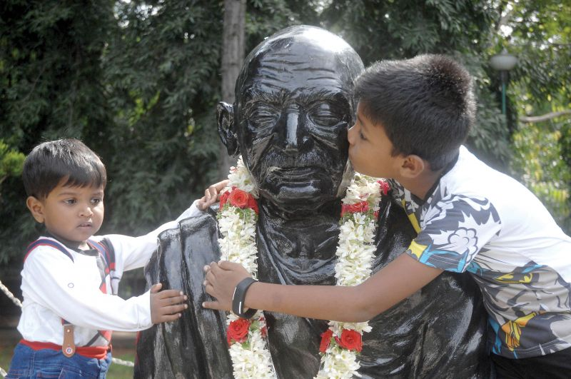 (Top) Boys hug the Gandhi statue on MG Road in Bengaluru on Tuesday. (Right) City Mayor Gangambike Mallikarjun garlands Gandhi statue on MG Road in Bengaluru on Tuesday (Image DC)