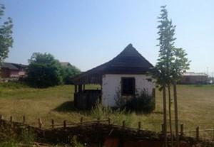 """Die einzige """"Baracke"""" von Pušča ist das Replikat eines historischen Hauses. Sie erinnert, wie die Steintafel auf dem Bild unten, an die Gründung der Siedlung 1911."""