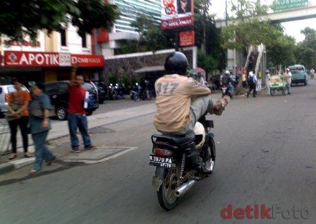 Orang ini melajukan sepeda motornya tanpa memegang setang motor. Fungsi tangan digantikan oleh kedua kakinya. :roll: