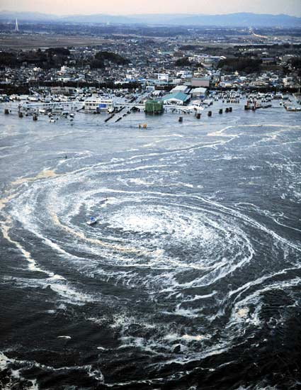 Sebuah perahu tampak terjebak di pusaran air Gempa Tsunami Jepang 2011