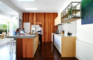 Kitchen, Refrigerator, Cooktops, Wood Cabinet, Concrete Counter, White Cabinet, Dark Hardwood, Recessed Lighting, Wall Oven, and Undermount Sink Australian expats Carla and Paul Tucker tasked designer Dan Gayfer with expanding their Melbourne bungalow without adding any square footage. In the kitchen, a soft palette of wood, laminate, and tile created cohesion, impressive considering the clients didn't see a single finish, color, or material in person prior to their homecoming. The kitchen cabinets were clad in Russian birch plywood, and the countertops were concrete.