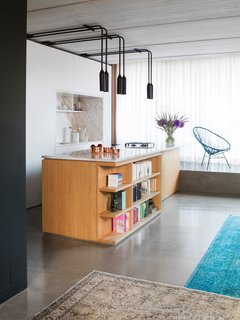 Kitchen, Concrete Floor, Rug, and Pendant Lighting By using color, wood, and polished concrete floors, this apartment in Berlin is full of personality. In the kitchen, polished statuario marble covers both the island's countertop and the backsplash in the custom kitchen cabinet block. PSLAB designed the light fixtures, and the island has open shelving incorporated into it for easy access to cookbooks and other reading material.