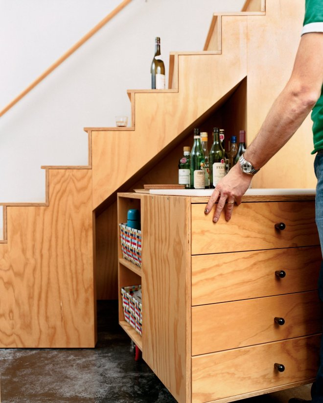 10 Smart and Surprising Under-Stair Design Solutions - Photo 2 of 10 - A mobile bar cart with room for kitchen storage is not the most traditional under-stair solution, but it's proven to be critical in the design of this kitchen and living space in Seattle by designer David Sarti. Its plywood construction, black knobs, and bright red casters mean that this design is meant to be noticed rather than be ignored.
