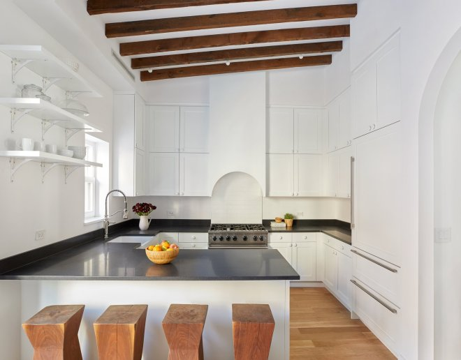 These 30 White Kitchens Are Anything But Ordinary - Photo 4 of 30 - A crisp, clean, eat-in kitchen with high-end appliances from Viking, Bosch, Sub-Zero, and LG make this space a chef's delight, while exposed beams, an arched stove hood, and a second arched carriage entrance along the back wall connect the room to the home's rich past.