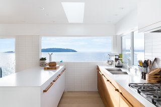 Kitchen A young Vancouver family asked Falken Reynolds Interiors to convert their waterfront vacation home on British Columbia's Sunshine Coast into their primary residence. To facilitate livability for the foursome, an enlarged kitchen, complete with a large white island with wood hardware, was a major part of the renovation.