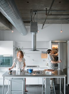 "Kitchen In Chicago's Lower West Side, editorial director Chelsea Jackson and and her chef husband Arthur renovated their fourth-floor condominium to include a custom Bulthaup kitchen. ""We wanted to find a kitchen island that would be light enough to make the room seem large while still standing up to heavy-duty cooking,"" Chelsea notes. Calls to kitchen retailers were fruitless until Arthur reached the Bulthaup showroom, where the staff suggested he come check out a floor model of the discontinued System 20 kitchen. The stainless steel island, with its precise profile and gas cooktop, was exactly what the couple was after, and they bought it on the spot. A full Bulthaup kitchen—completed with components from the B3 range—would soon become the centerpiece of their new home."