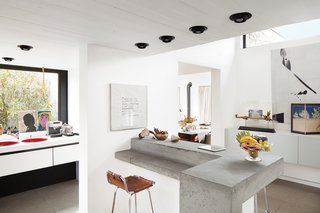 Kitchen, Concrete Counter, and Recessed Lighting Smitten from the start with a 1970s concrete villa in rural Belgium, a resident and her designer embark on a sensitive renovation that excises the bad (carpeted walls, dark rooms) and highlights the good (idyllic setting, statement architecture). Owner Nathalie Vandemoortele worked with designer Renaud de Poorter on the interior renovations, which included opening up the heavy structure with the help of new windows and doors to the outside. A concrete bi-level island keeps the Brutalist vibe on the interior, but is open and light enough to feel balanced.