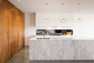 Kitchen, Marble Counter, White Cabinet, Concrete Floor, Wood Cabinet, Pendant Lighting, Undermount Sink, Recessed Lighting, and Cooktops The entire living and dining space features tough polished concrete floors. The architects intentionally contrasted the darker concrete and veneered pantry against the neutral white walls and marble. This color play runs through the renovated areas.