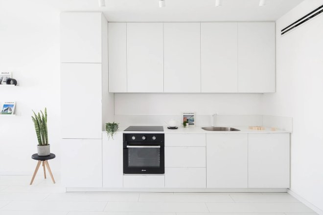 These 30 White Kitchens Are Anything But Ordinary - Photo 16 of 30 - A minimalist interior located in Tel-Aviv, Israel, has been designed by Yael Perry. The apartment was renovated and includes a bright living space, kitchen, and one bedroom, along with a wide bathroom. The designer, who wanted to provide a unique aesthetic that also made the space feel more spacious and bright, chose to design the apartment in one shade of color: white.