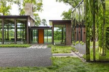 "Glass House And ""shiny Shed"" Merge With Nature In"