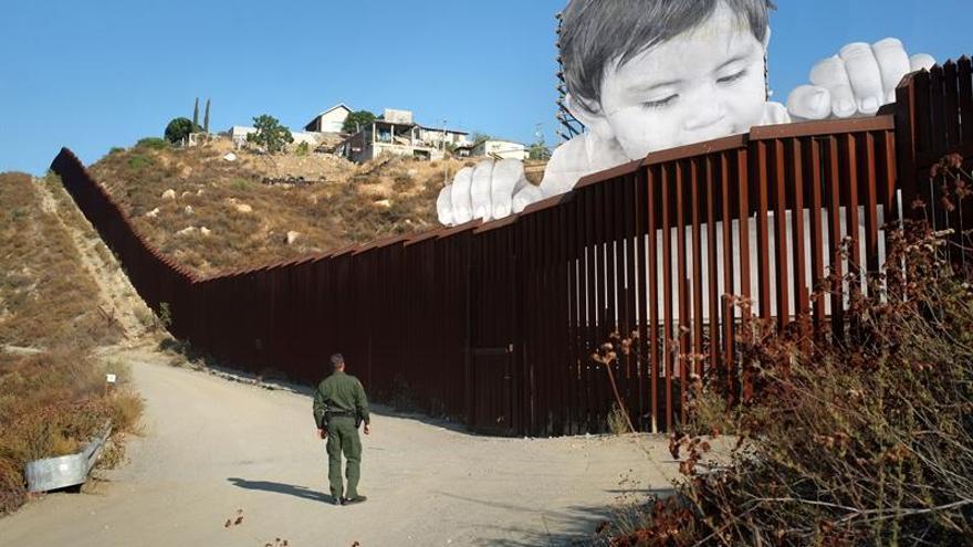 Un artista francés levanta a un niño gigante entre la frontera de EE.UU. y México