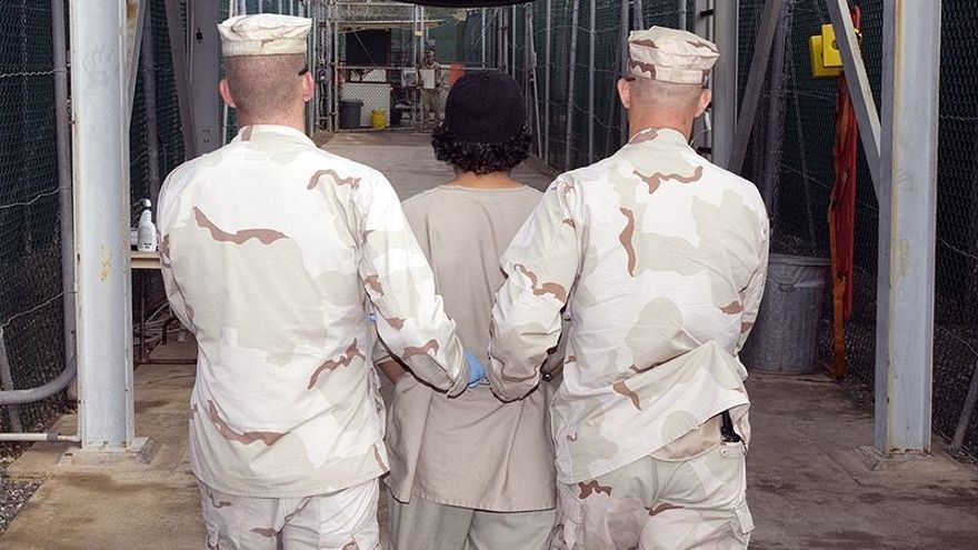 Dos soldados trasladan a un detenido en un campo de prisioneros de Guantánamo. Foto: Wikimedia