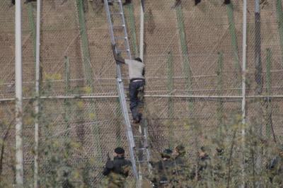Una de las personas que estaban encaramadas desciende por una escalera situada en suelo español y es devuelta de forma ilegal posteriormente./ Foto: Efe