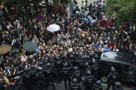 Spanish National Police prevents people from entering a voting site at a school assigned to be a polling station by the Catalan government in Barcelona, Spain, Sunday, 1 Oct. 2017. Catalan pro-referendum supporters vowed Saturday to ignore a police ultimatum to leave the schools they are occupying to use in a vote seeking independence from Spain.