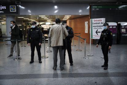 Agentes de la Policía Nacional controlando el DNI de los pasajeros en la estación de tren de Atocha en Madrid.