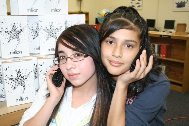 Students hold Burner cellphones up to their ears. They earn minutes by completing their reading programs
