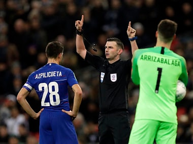 Referee Michael Oliver, center, signals for video review as Chelsea's Cesar Azpilicueta, left, and Chelsea's goalkeeper Kepa Arrizabalaga look on during the English League Cup semifinal first leg soccer match between Tottenham Hotspur and Chelsea at Wembley Stadium in London, Tuesday, Jan. 8, 2019. (AP Photo/Kirsty Wigglesworth)