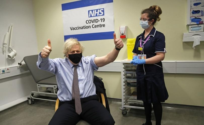 British prime minister Boris Johnson gestures after receiving the first dose of the AstraZeneca vaccine. Photo via AP/Frank Augstein