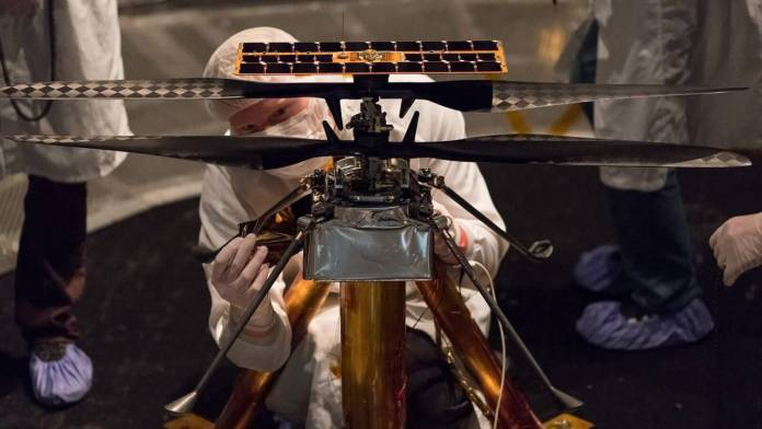 The Ingenuity team attaches a piece to the flight model in early 2019. Image: NASA/JPL-Caltech