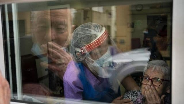 In Spain, an elderly couple separated after the pandemic overcome grief through a glass pane