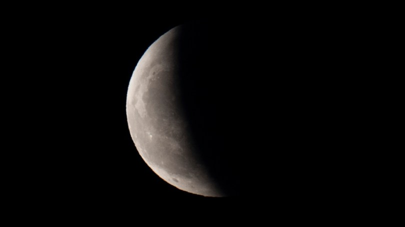 The earth's shadow partially obscures the moon as it emerges from behind a cloud during a lunar eclipse in the skies over Beijing. China. Image credit: AP Photo/Ng Han Guan)