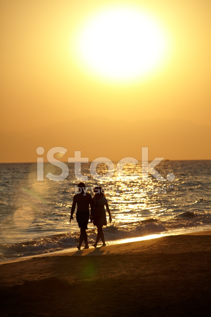 Silhouette Of Love Couple Walking On Beach Stock Photos