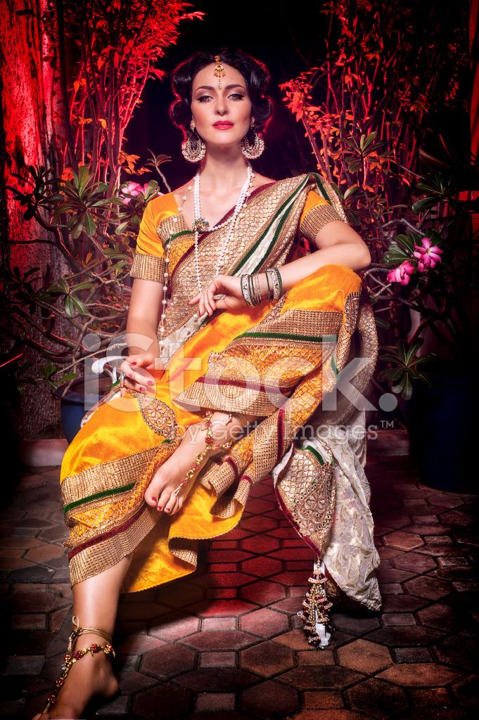 Indian Beautiful Girl Sitting IN IN A Yellow Saree Stock