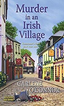framsiden til Murder in an Irish Village, illustrasjon av en gate med brostein og rekker med fargerike hus. En veltet blomstervase (med blomster) ligger i gaten