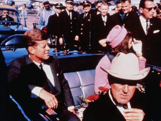(Original Caption) Texas Governor John Connally adjusts his tie (foreground) as President and Mrs. Kennedy, in a pink outfit, settled in rear seats, prepared for motorcade into city from airport, Nov. 22. After a few speaking stops, the President was assassinated in the same car.