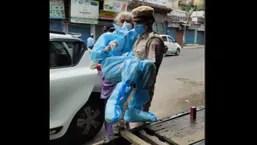 Delhi Police constable Kuldeep Singh carrying Shaila D'Souza to the vaccination centre.