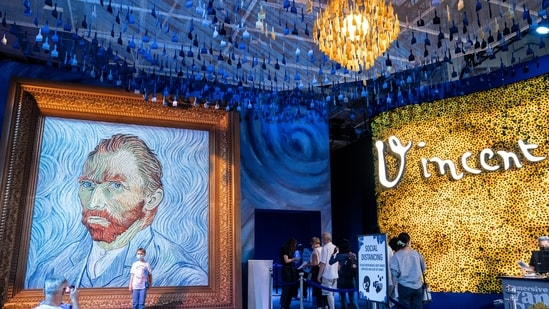 Guests arrive beside a giant replica of celebrated painter Vincent Van Gogh's self portrait during a preview of the Immersive Van Gogh exhibit at Pier 36, Friday, June 4, 2021, in New York. (AP)