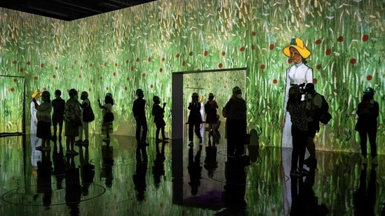 """People attend a media preview of the """"Immersive van Gogh"""" exhibit at Pier 36 on May 26, 2021 in New York City. - The art installation displays iconic works of post-Impressionist artist Vincent van Gogh, evoking his emotional and chaotic inner consciousness through art, light, music and movement. (AFP)"""