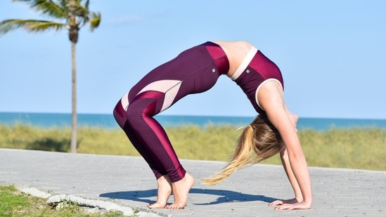 1.Chakrasana or backbend: Lie down on your back and fold your legs at your knees to ensure that your soles are placed firmly on the floor and closer to your buttocks. Keep your feet hip-width apart and your palms facing the sky. Inhale, balance your weight on your limbs and lift your entire body up to form an arch. Relax your neck keeping it long and allow your head to hang gently behind. Hold onto the pose for as long as you are comfortable and then release by bending your arms, legs and gently lowering your back on the ground. Lie down in Shavasana for a few minutes before resuming. Caution: Perform this only when your stomach and bowels are empty.(Photo by Jose Mizrahi on Unsplash)