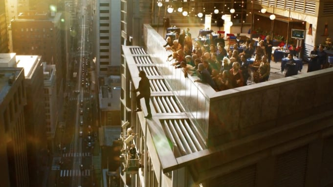 A character that appears to be Neo taking a step from a tall building.