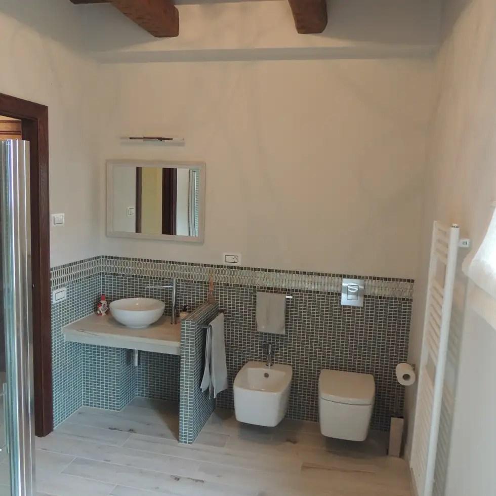 Bagno piano terra con pavimento in ceramica effetto legno e rivestimento a media altezza in
