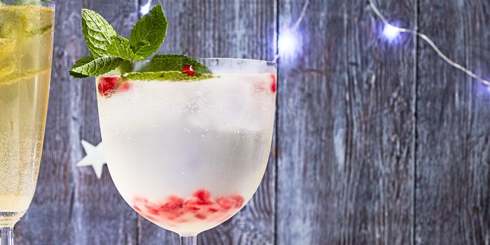 Cocktail with pomegranate seeds and herbs