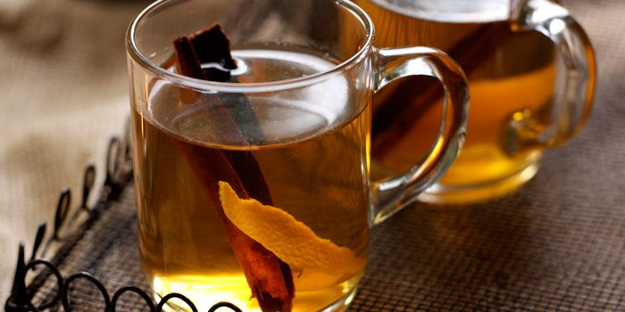 Apple juice in glasses with cinnamon and orange