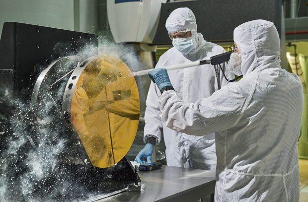 मॉल डस्ट पार्टिकल्स विज्ञान को प्रभावित कर सकते हैं जो JWST करने में सक्षम है, इसलिए प्राचीन दर्पण महत्वपूर्ण हैं।  यहाँ इंजीनियर कार्बन डाइऑक्साइड बर्फ का उपयोग करके परीक्षण दर्पण खंड को साफ करने और सतह को खरोंच किए बिना दूषित कणों को हटाने का अभ्यास करते हैं। © NASA / Goddard Space Flight Centre