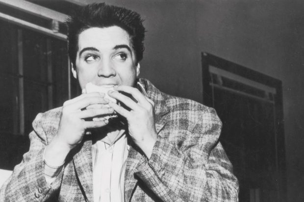 American singer and actor Elvis Presley eating a sandwich