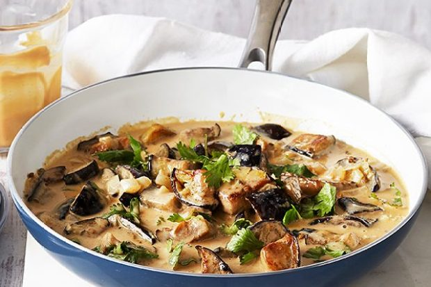 Bowl of creamy aubergine curry with a plate of forks at the side