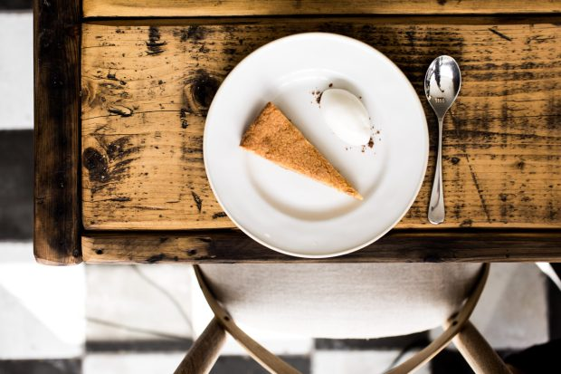 A slice of Bakewell tart and a quenelle of ice cream are sat on a white plate. The plate is on a distressed wooden table and the photo is taken overhead